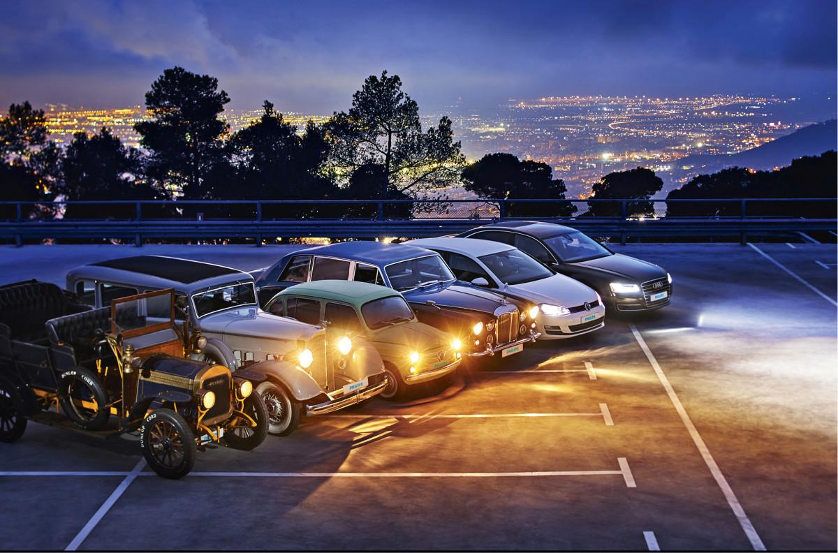 Kynttilänvalosta päivänpaisteeseen. Kentän hämärää reunaa valaisee karbidilampuillaan vuoden 1909 Reyrol vierellään 1934 Packard, 1964 Seat 800, 1968 Daimler DS420, 2014 VW Golf valkoisin halogeenein ja viimeisenä ledein varustettu 2014 Audi A8.
